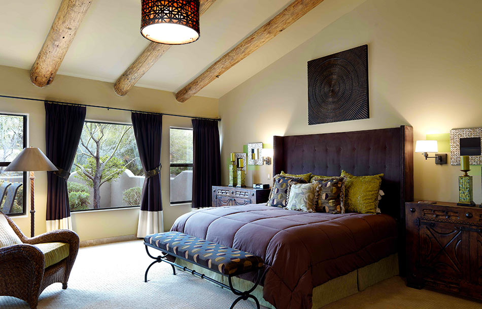 King-sized bed with luxury bedding and wooden ceiling beams